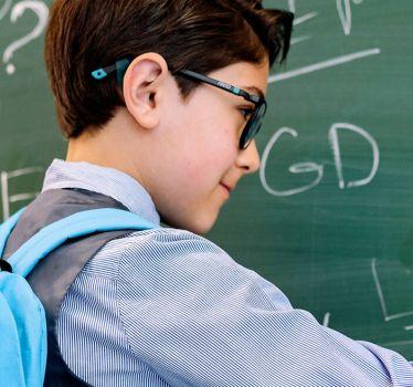 Chłopiec z plecakiem pisze na tablicy
